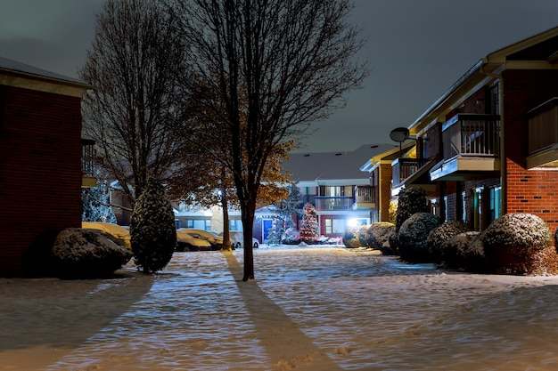 Зимний ночной пейзаж - скамейка под зимними деревьями и уличные фонари с падающими снежинками Premium Фотографии