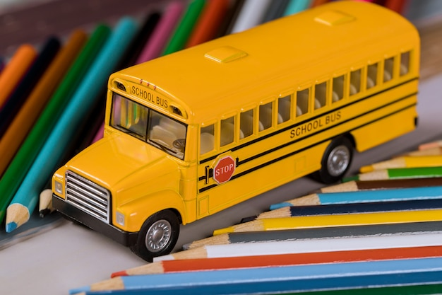 色の木製鉛筆でおもちゃのスクールバス。 Premium写真
