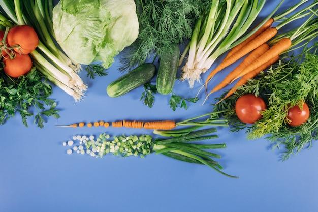 Свежие овощи для салата на синем фоне. Premium Фотографии