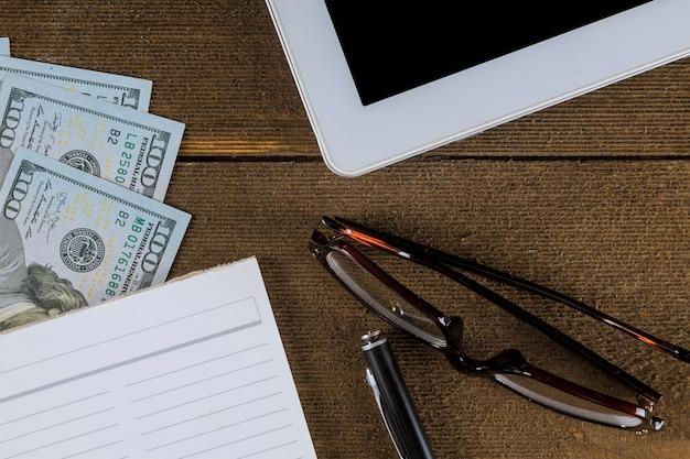 木製のテーブル-空のノートとペン、ドル札、眼鏡の上からビジネスビュー Premium写真
