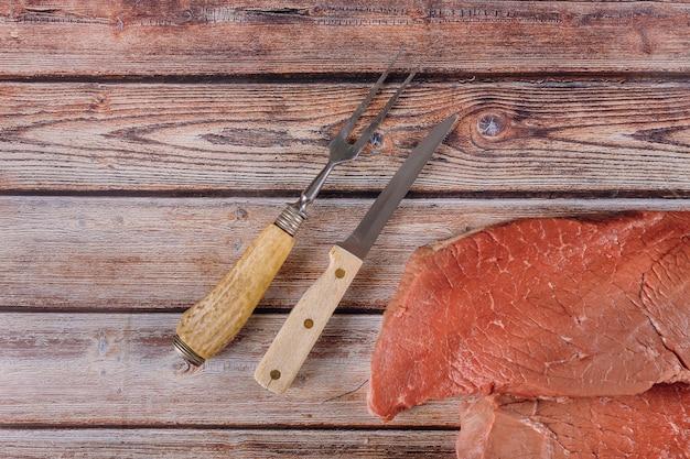 木製のテーブルにナイフで新鮮な生の牛肉ステーキ Premium写真