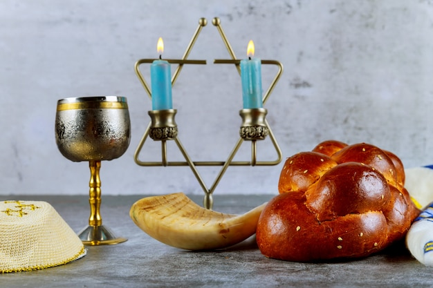 Шаббат с хлебом халы на деревянном столе свечи и чашка вина. Premium Фотографии