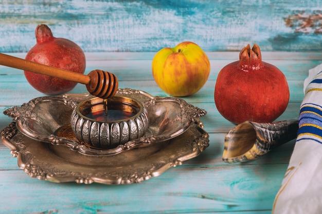Шофар и талит со стеклянной банкой меда и свежими спелыми яблоками. еврейские новогодние символы. рош ха-шана Premium Фотографии