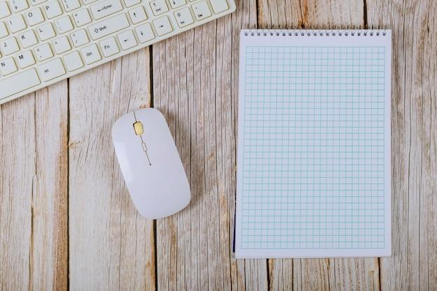 空白のノートブックと木製のテーブル背景にキーボードのオフィスのテーブル。 Premium写真