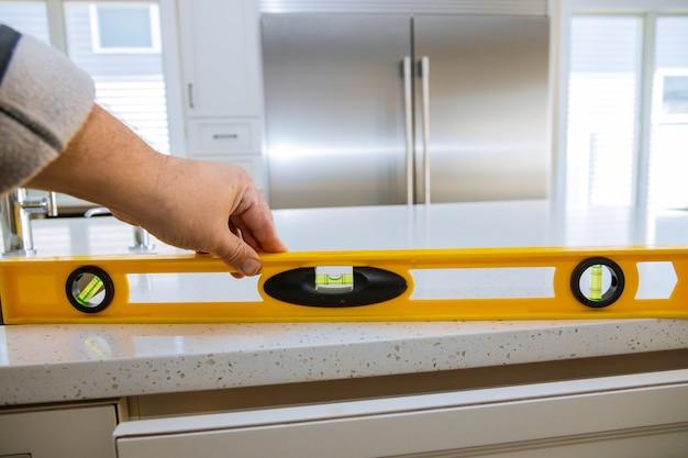 Рабочий проверяет выравнивание гранитных столешниц в домашней кухне переделывают Premium Фотографии