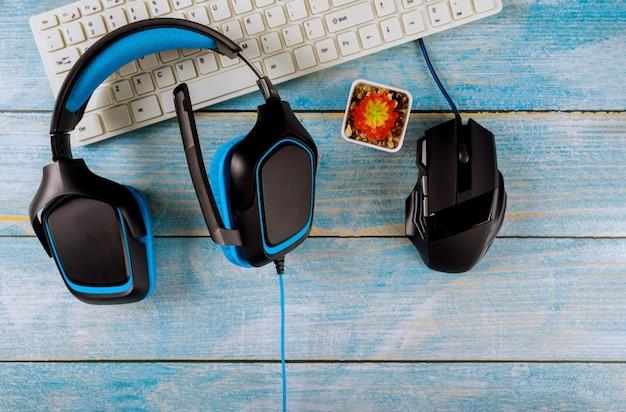 ゲームウッドヘッドフォンと古い木製の青いテーブルの上のマウスとキーボード Premium写真