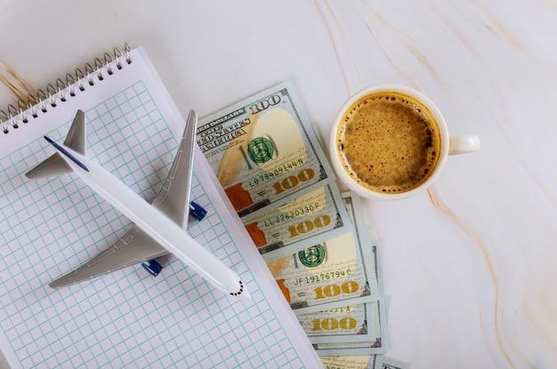 Каникулы, планирование ноутбука с самолетом, праздник, банкноты доллара сша, чашка кофе с самолетом в отпуске Premium Фотографии