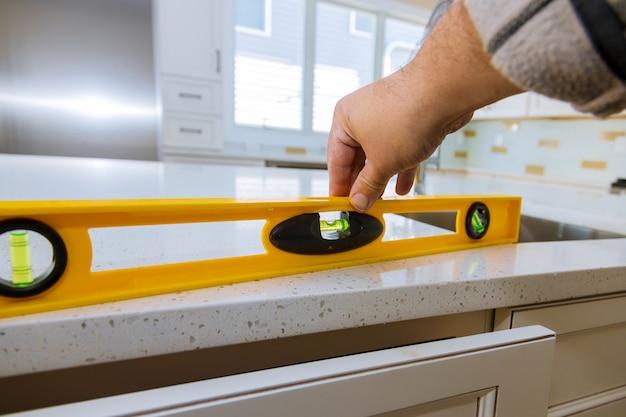 現代の家庭用キッチンキャビネットを作るカウンタートップでレベリング Premium写真