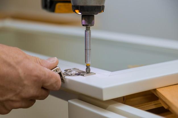 大工のインストーラーキャビネットドアヒンジ改善ビューインストール新しいキッチン Premium写真