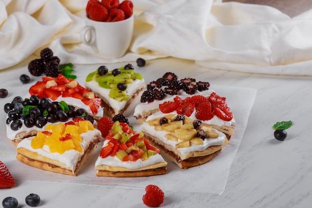 Клубнично-кремовый бисквит на домашнем летнем десерте на деревянном столе Premium Фотографии