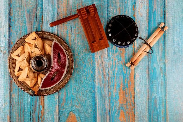 ハマンタッシェンクッキーハマンス耳、カーニバルマスク、羊皮紙キッパ、ホーン、素朴な背景の上のユダヤ人の休日プリム Premium写真