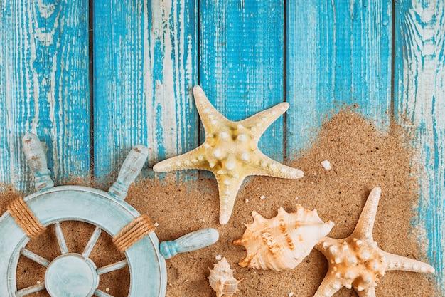 Летние путешествия каникулы моряка капитана колеса морская звезда и ракушка на песке Premium Фотографии