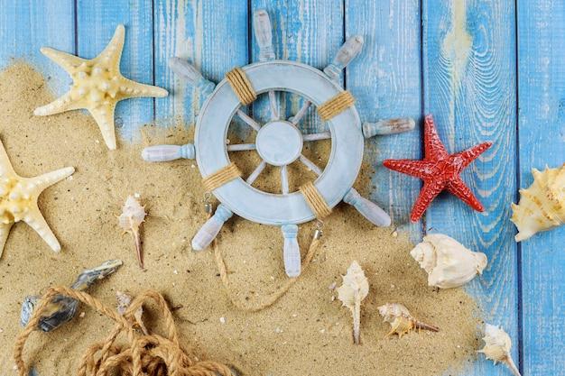 Декоративный руль с морскими звездами, ракушками на песчаном пляже на синем фоне дерева Premium Фотографии