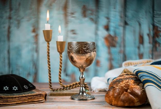 Субботний еврейский праздник халы хлеб и канделы на деревянный стол Premium Фотографии