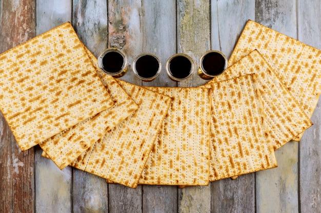 Пасха мацы еврейского праздника хлеб, четыре бокала кошерного вина за деревянным столом. Premium Фотографии