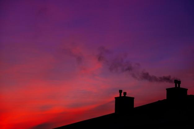 Вид с воздуха на пейзаж с крышами, восход солнца в первой половине дня. снежные домики с дымом Premium Фотографии
