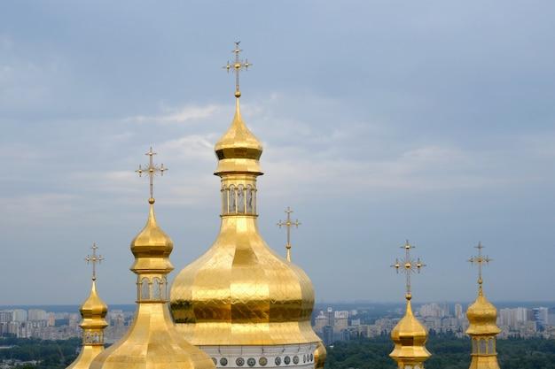 正統派キリスト教修道院。中世の大聖堂とキエフ・ペチェルシク大修道院の教会の黄金のドーム、雲と青い空。歴史的な文化の聖域。 Premium写真