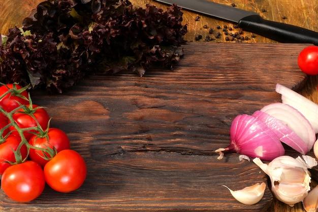 自家製料理。おいしい食べ物の製品。野菜:トマト、レタス、タマネギ、ニンニク、木製キッチンボードにあります。 Premium写真