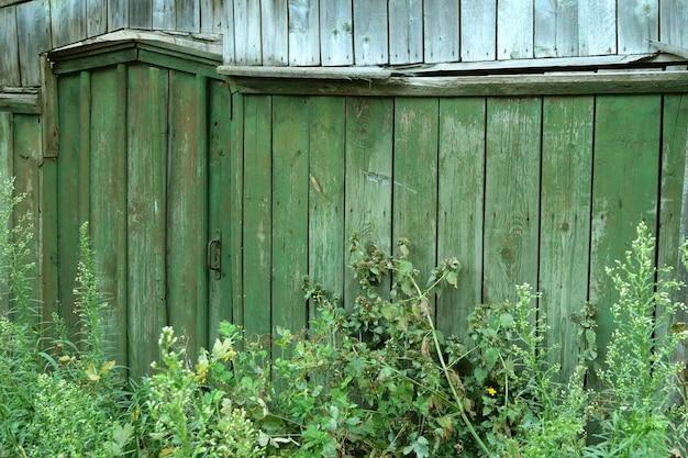 閉じられた、草で覆われたドアまたは田舎の木製の緑のフェンスの改札口。田園風景。 Premium写真