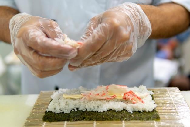 レストランで寿司を調理します。手のクローズアップ Premium写真