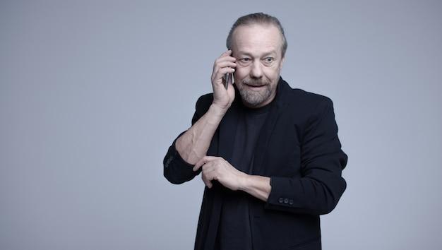 陽気な老人が電話で話しています。 Premium写真