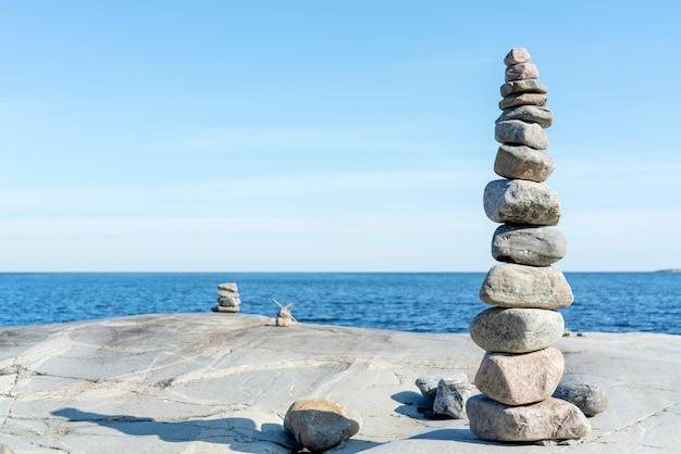 Штабелированные скалы уравновешивают, укладывают с точностью. каменная башня на берегу. копировать пространство Premium Фотографии