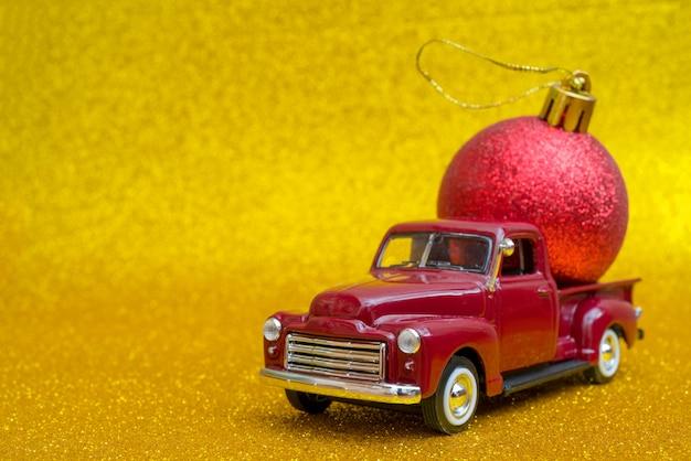 おもちゃの車は、休日のクリスマスグッズボールを運ぶ Premium写真