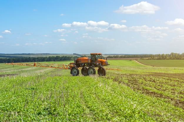 自走式噴霧器は、雲がある青空の下の畑で働く Premium写真