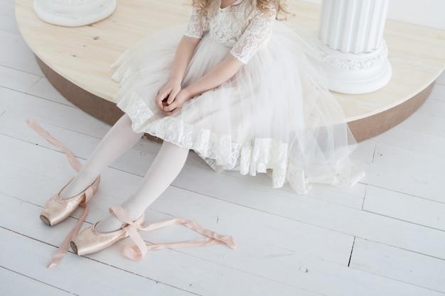 白い緑豊かなドレスの小さなバレリーナはトウシューズを履いています Premium写真