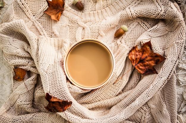 ウールベージュセーターに包まれたコーヒーカップ Premium写真