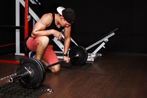 デッドリフト。ジムでバーベル行を持ち上げるスポーツ男 Premium写真