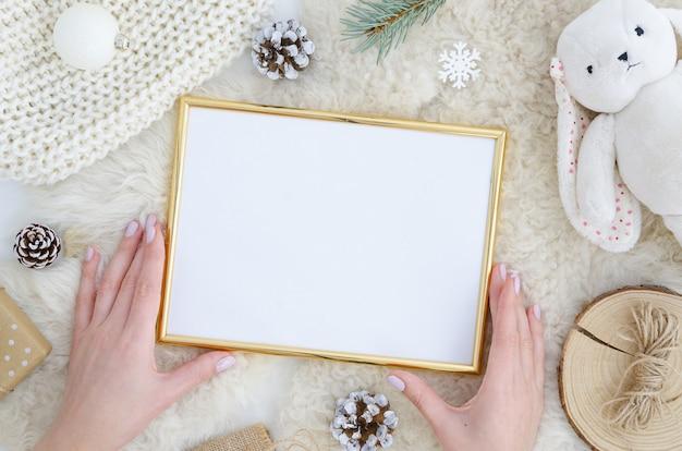 女の子の手はゴールドフォトフレームモックアップを保持していますクリスマス、新年の背景 Premium写真