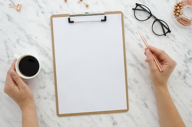 空白のホワイトペーパーシートを大理石の背景にモックアップクリップボード Premium写真