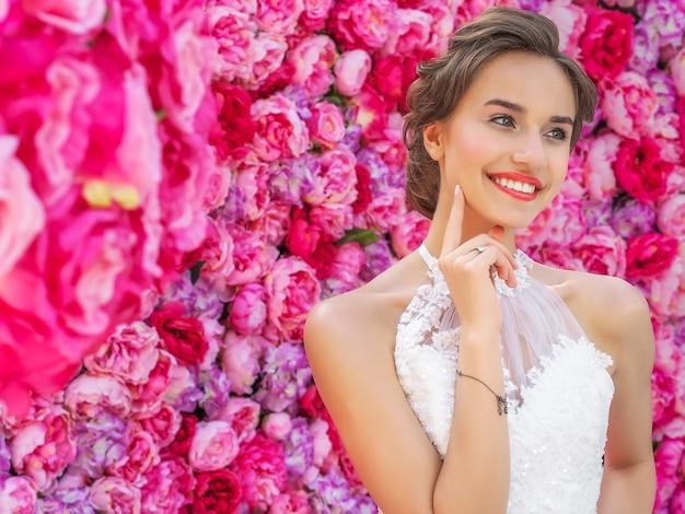 装飾的なピンクの花でポーズのウェディングドレスの美しい花嫁 Premium写真