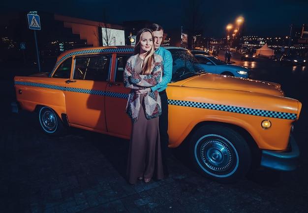 Пара возле желтой машины такси в ночное время на улице города Premium Фотографии