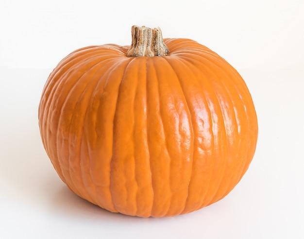 Маленькая оранжевая тыква, изолированная на белом Premium Фотографии