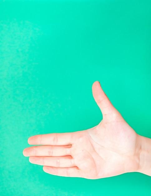 分離ターコイズグリーン色の背景上の女性の手 Premium写真