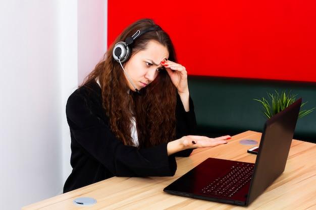 Портрет женского оператора на компьютере в офисе. Premium Фотографии