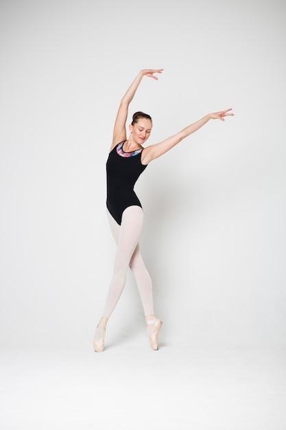 バレリーナは白い背景の拍でダンスのポーズで立っています。 Premium写真