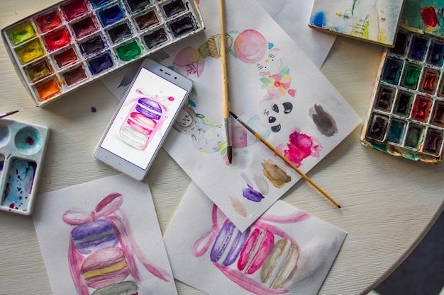 Акварельные рисунки на столе с красками крупным планом Premium Фотографии