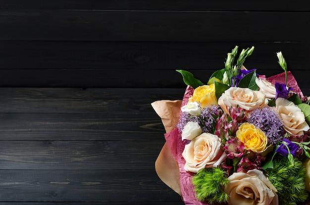 Букет цветов на темном деревянном фоне. букет с розами. Premium Фотографии