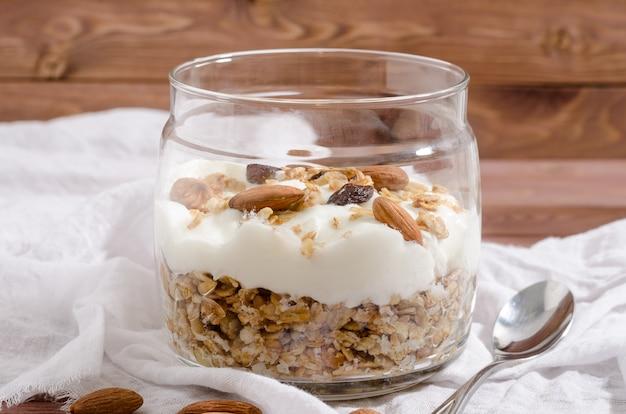 Мюсли с натуральным йогуртом, орехами и сухофруктами в стеклянной банке Premium Фотографии