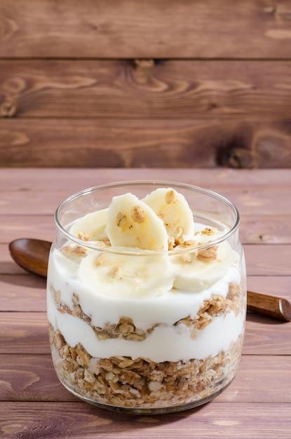 Мюсли с натуральным йогуртом, бананом, орехами и сухофруктами в стеклянной банке Premium Фотографии