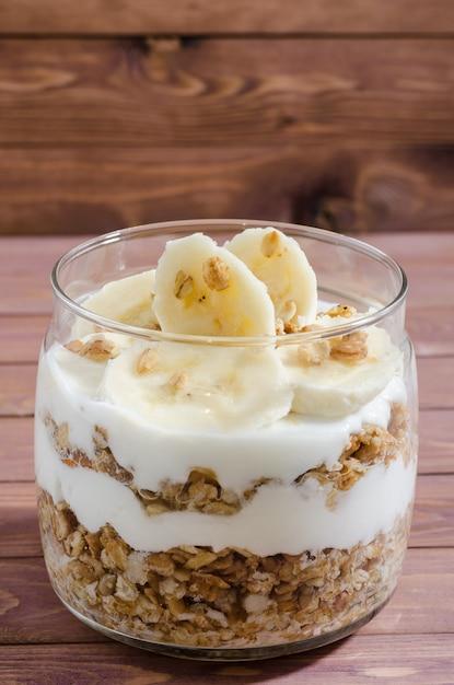 天然ヨーグルト、バナナ、ナッツ、ドライフルーツをガラス瓶に入れたミューズリー Premium写真