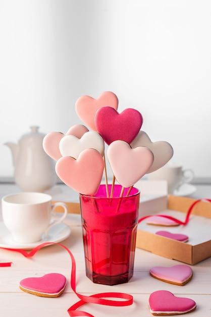 ライトテーブルの上の明るいピンク色のガラスのハートの形の棒にジンジャーブレッド。バレンタイン・デー。 Premium写真