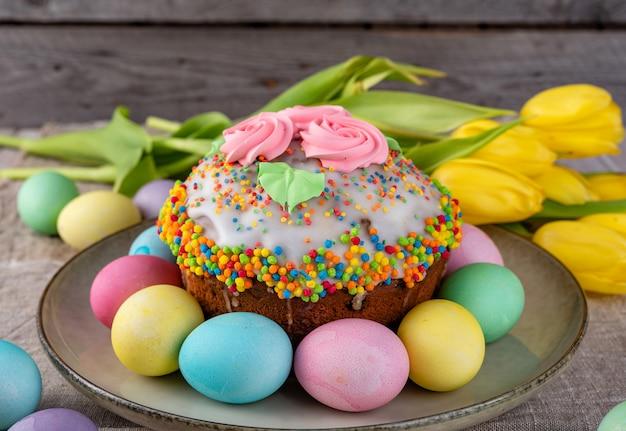 イースターケーキ、木製の古い素朴な背景のチューリップと卵を描いた。 Premium写真