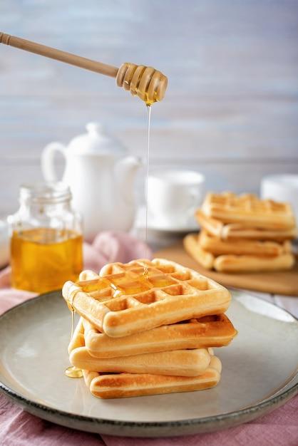 Вафли с медом на светлом фоне Premium Фотографии