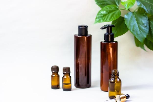 暗い化粧品ボトルと明るい背景に緑の自然の葉 Premium写真