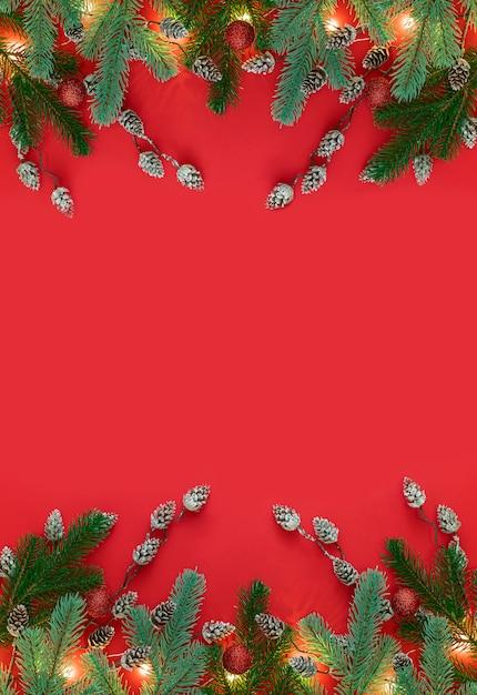 モミの木、小枝のクリスマスツリー、茶色の松ぼっくりのフレームとクリスマスの背景。上面図 Premium写真