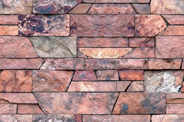 Бесшовный фон из декоративной гранитной плитки. картина каменной стены для внешней и внутренней отделки. красный гранитный камень Premium Фотографии